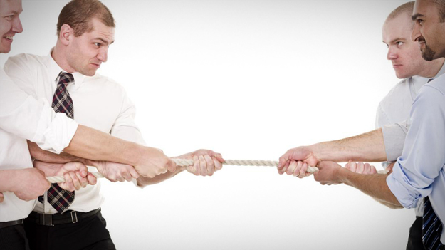 Employees pulling at a rope to illustrate political tension in the office in an HR trends blog