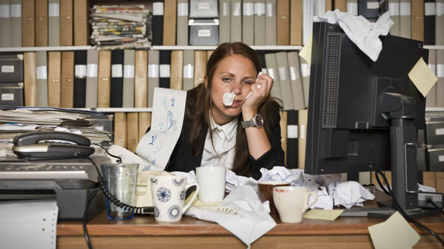 Picture of sick business woman with cluttered desk to show importance of fighting flu in workplace in a HR trends blog