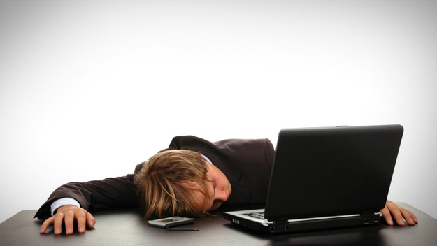 Picture of businessman asleep in front of laptop to illustrate information overload in the HR trends blog