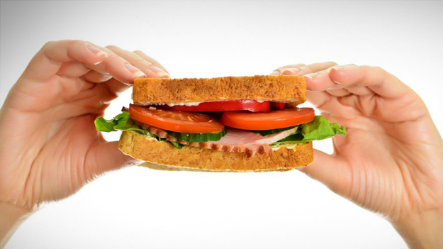 Photo of person holding sandwich to illustrate the sandwich generation in the HR trends blog