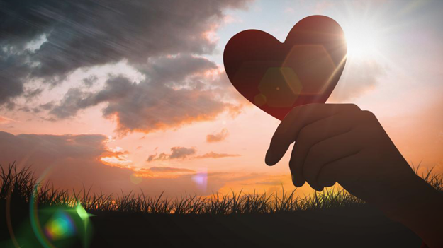 Picture of woman holding up a heart in a sunset to illustrate the importance of women making health a priority in a HR trends blog