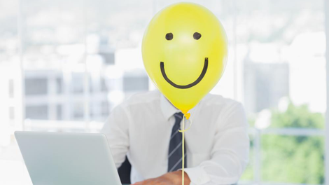 Businessman covered by yellow balloon with smiley face to illustrate importance of wellness programs in employee benefit resources