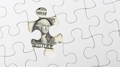 Puzzle revealing dollar bill to illustrate importance of investment management in employee benefit resources