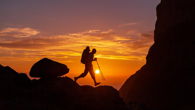Hiker at sunset illustrating how retirement plan services are necessary to benefit your financial resources